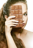 Chocolate. beautiful girl looking behind chocolate Stock Photos