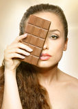 Chocolate. beautiful girl looking behind chocolate, woman model one eye looking Stock Image