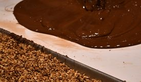 Chocolate being poured next to almonds stock photos