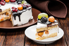 Chocolate berry cake slice on plate over brown wooden background Stock Photos