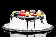 Chocolate berry cake on stone plate over black background Royalty Free Stock Photos