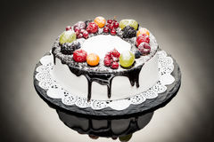 Chocolate berry cake on stone plate over black background Stock Image