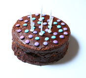 Chocolate birthday cake with blue and violet candies on white background Royalty Free Stock Photos