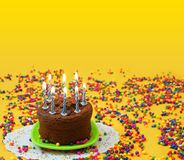 Chocolate birthday cake with lighted blue and white candles, on a small green plate surrounded by candy balls strewn on a yellow b royalty free stock images