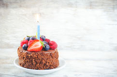 Chocolate birthday cake with candle, raspberries, blueberries an Royalty Free Stock Photography