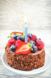 Chocolate birthday cake with candle, raspberries, blueberries an Royalty Free Stock Image