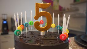Chocolate birthday cake with candles and number five stock video