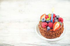 Chocolate birthday cake with candles, raspberries, blueberries a Royalty Free Stock Photo