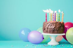 Chocolate birthday cake with colorful candles. And balloons Stock Photography