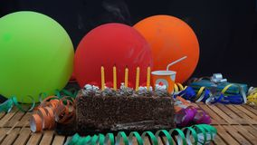 Chocolate birthday cake with five yellow candles extinguished on rustic wooden table with background of colorful balloons. Gifts, plastic cups and streamers stock photo