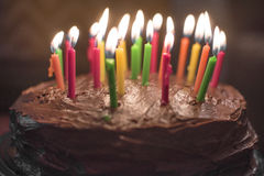 Chocolate birthday cake isolated with candles Royalty Free Stock Photo