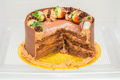 Chocolate birthday cake, partly eaten in a refigerator. Stock Photos