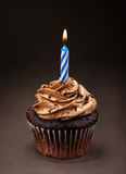 Chocolate Birthday Cupcake. A chocolate cup cake with icing, sprinkles and a lit birthday candle royalty free stock photos