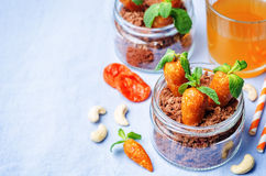 Chocolate biscuit in a jar and dried apricots cashew candies in. The form of carrots for children for Easter. toning. selective Focus Stock Photo