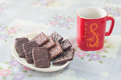 Chocolate biscuits with a Chinese style glass. Chocolate biscuits with the white red Chinese style glass on the white table Royalty Free Stock Image