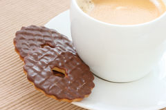 Chocolate biscuits on saucer with coffee. Close up view of two chocolate biscuits on white saucer with espresso coffee Royalty Free Stock Photo