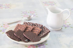 Chocolate biscuits with the white jug. And spoon on the white table Stock Images