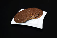 Chocolate biscuits on a white plate. Black background Stock Photo