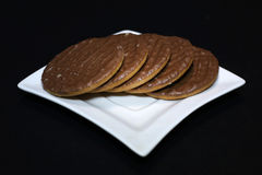 Chocolate biscuits on a white plate. Black background Royalty Free Stock Photos