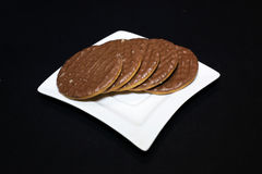 Chocolate biscuits on a white plate. Black background Stock Images