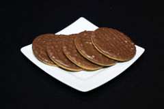 Chocolate biscuits on a white plate. Black background Stock Photography