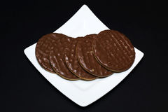 Chocolate biscuits on a white plate. Black background Royalty Free Stock Images