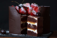 Chocolate bisquit cake with strawberries and cherries. Sweet dishes Royalty Free Stock Photos