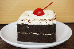 Chocolate black forest cake. Colorful chocolate black forest cake decorated with cherry on wooden background, close up Stock Images