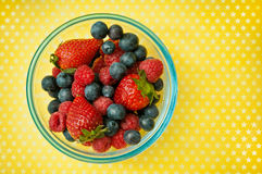 Chocolate. Blueberies, strawberries and raspberries in a bowl over yellow background with copy space stock image