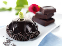 Chocolate bomb pastry with a red rose. A chocolate dessert covered with glazed chocolate sauce and a sugar leef decorated with a red rose and three pieces of royalty free stock image