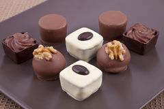 Chocolate bonbon pralines. On a brown plate Stock Images