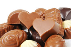 Chocolate bonbons. A pile of different chocolate bonbons, some of them heart-shaped, on a white background Royalty Free Stock Images