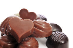 Chocolate bonbons. A pile of different chocolate bonbons, some of them heart-shaped, on a white background Royalty Free Stock Photo