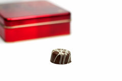 Chocolate box. Image of a piece of chocolate and in the background a red box.Selectve focus on the chocolate Stock Images