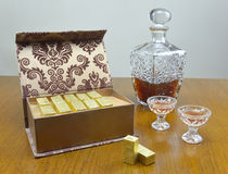 Chocolate box and liquor bottle. Chocolate box, liquor bottle, glasses with liquor on wooden table Royalty Free Stock Image