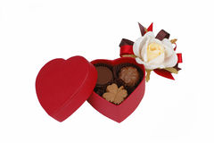 Chocolate box still life. Red heart shape chocolate box and white rose isolated over white background Stock Image