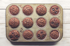 Chocolate bran muffins with cherries, in old, grunge looking, tin tray. Top view Stock Photos