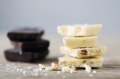 Chocolate branco e escuro em uma tabela de madeira Fotografia de Stock