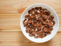 Chocolate breakfast cereal in a white bowl on wooden table. With copy space. Top view. Healthy breakfast concept royalty free stock photos