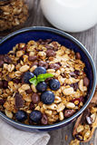 Chocolate breakfast granola in a bowl. Chocolate breakfast granola with milk and blueberries Royalty Free Stock Photos
