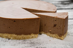 Chocolate brown cheesecake and slice on wooden. Table Stock Photography