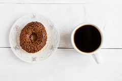Chocolate brown donut on white wooden table and cup of black coffee, top view.  Royalty Free Stock Images