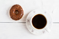 Chocolate brown donut on white wooden table and cup of black coffee, top view.  Royalty Free Stock Photography