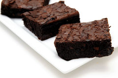 Chocolate Brownie. Sweet and tasty chocolate brownies served on a white rectangular plate against a light colored background Stock Photos