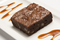 Chocolate brownie. Portion of chocolate brownie on a white plate Stock Image