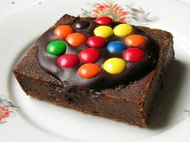 Chocolate brownie. A chocolate brownie covered with candies, on a floral white plate stock photos