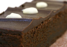 Chocolate Brownie. With white icing drops, narrow depth of field Stock Photos