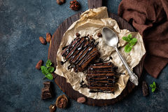 Chocolate brownie cake, dessert with nuts on dark background, directly above. Flat lay royalty free stock photos