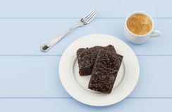 A chocolate brownie and a coffee cup Royalty Free Stock Photos