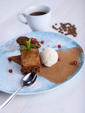 Chocolate brownie with ice cream on a blue plate. Next to a cup of coffee. Chocolate cake with coffee Royalty Free Stock Photography